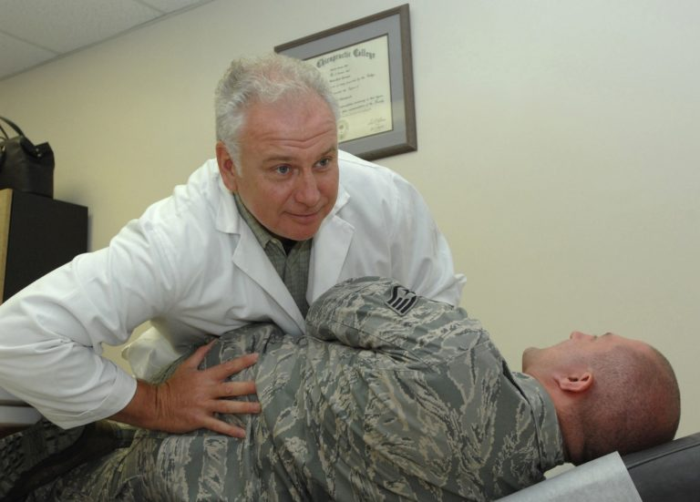 doctor helping soldier's back with orthopedic issues
