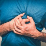 man clutching chest due to chest pain caused by cardiovascular disease