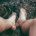 person with legs in water to treat arthritis in ankle