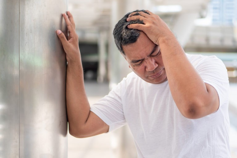 senior asian man leaning on wall with head covered by left hand due to vertigo