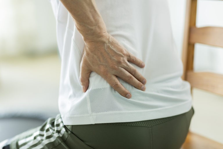 person clutching waist while sitting down caused by hip pain